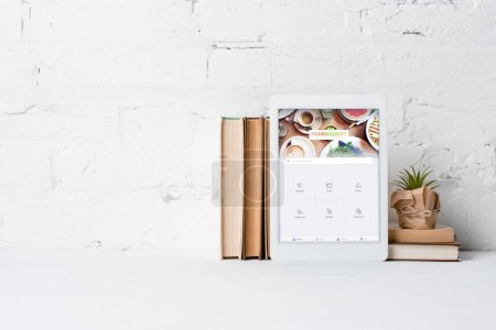 Photo for Digital tablet with foursquare application, books and potted plant near white brick wall - Royalty Free Image