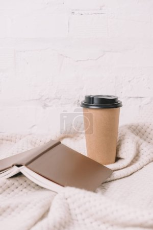 Photo for Close-up view of book and disposable coffee cup on white blanket - Royalty Free Image