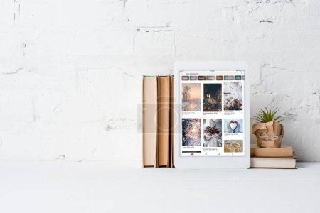 Photo pour Tablette numérique avec application pinterest, livres et plantes en pot près du mur de briques blanches - image libre de droit