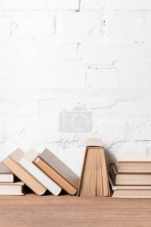 Foto de Libros con los hardcovers en mesa de madera junto a la pared de ladrillo blanco - Imagen libre de derechos