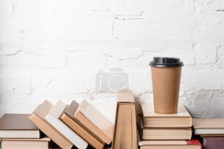 Photo pour Livres avec couvertures rigides et café pour aller près mur de briques blanches - image libre de droit