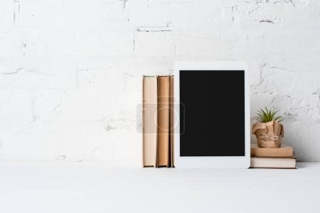 Photo pour Tablette numérique avec écran blanc, plante en pot et livres près de mur de briques blanches - image libre de droit