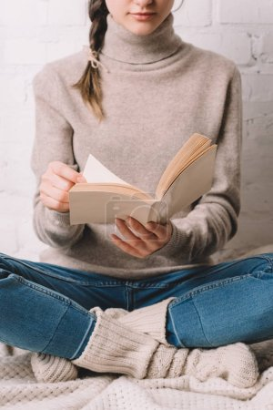 cropped shot of girl in knitted socks sitting and reading book