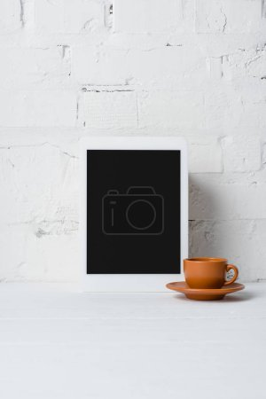 close-up view of digital tablet with blank screen and cup of coffee near white brick wall