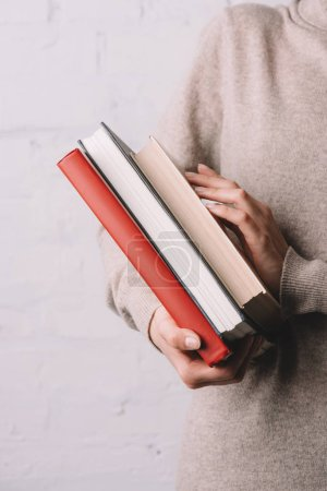 close-up partial view of young woman holding books