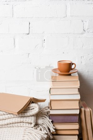 Photo for Cup of coffee on pile of books near white brick wall - Royalty Free Image