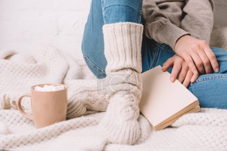 cropped shot of girl in knitted socks sitting with book on warm blanket