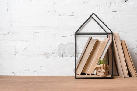 books, green potted plant and house model decoration on wooden table