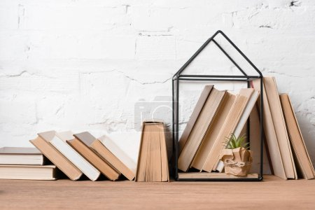 books and green potted plant in house model decoration on wooden table