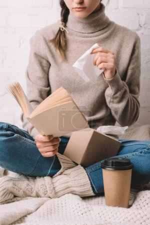 cropped shot of woman holding paper tissue and reading book
