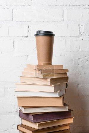 Photo pour Café pour aller sur pile de livres près de mur de briques blanches - image libre de droit