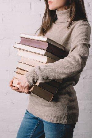 Photo pour Plan recadré de jeune femme tenant pile de livres - image libre de droit