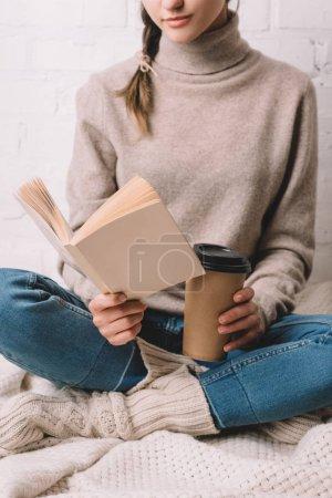 Photo pour Plan recadré de fille tenant tasse en papier et livre de lecture - image libre de droit