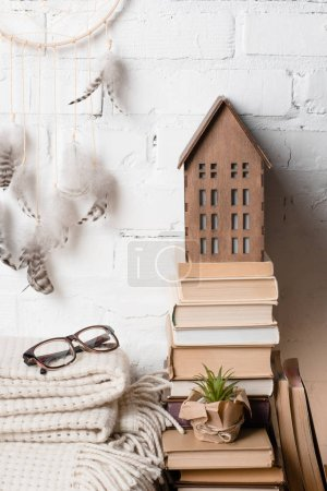 books, dream catcher, eyeglasses and decorative wooden house near white brick wall