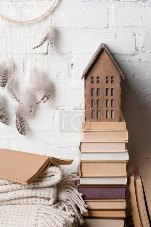 books, dream catcher and decorative wooden house near white brick wall