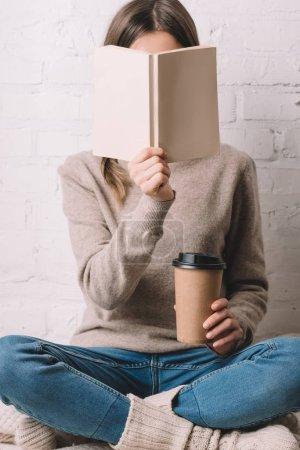 Photo pour Fille tenant le livre et le café pour aller dans la tasse en papier - image libre de droit