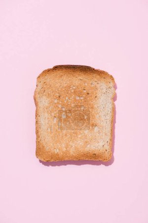 top view of crunchy toast on pink surface