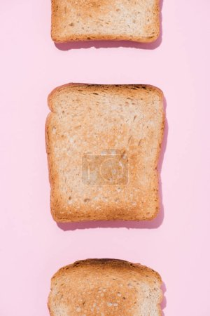 top view of row of crunchy toasts on pink surface