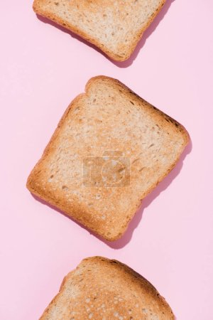 Photo for Top view of row of delicious toasts on pink tabletop - Royalty Free Image