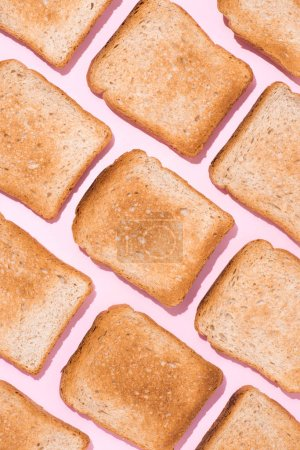 top view of pattern of crunchy toasts on pink surface