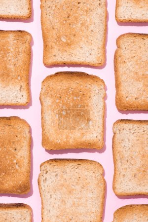 top view of pattern of crispy toasts on pink surface
