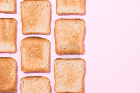 Draufsicht auf Reihen knuspriger Toasts auf rosa Oberfläche