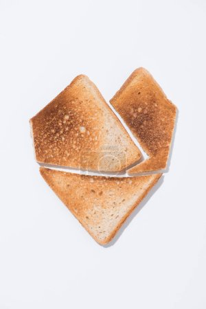 top view of heart shape made of toast on white surface