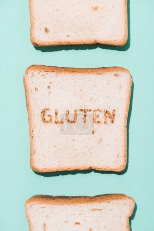 top view of row of bread slices with gluten sign on blue surface