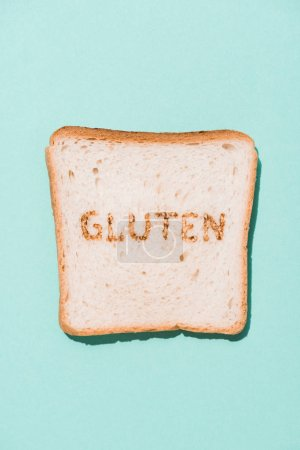 top view of row of bread slice with gluten sign on blue surface