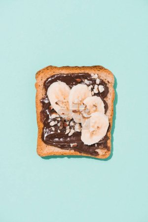 top view of delicious toast with chocolate paste and banana on blue surface