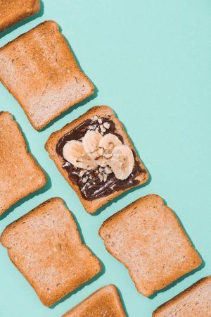 top view of toasts with chocolate paste and banana on blue surface
