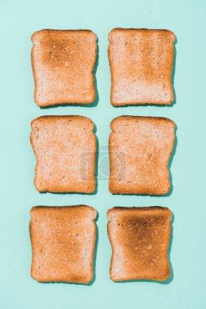 Draufsicht auf montierte knusprige Toasts auf blauer Oberfläche
