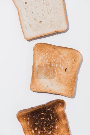 top view of toasts in various roast stages on white surface