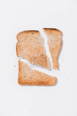 top view of teared toast on white surface
