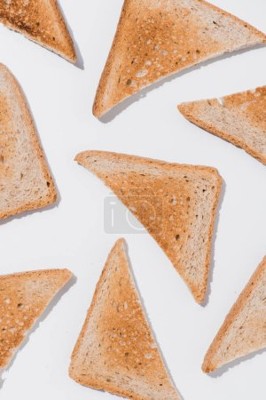 top view of toasts cut in triangles on white surface