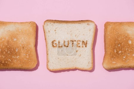top view of row of toasts and slice of bread with burned gluten sign on pink surface