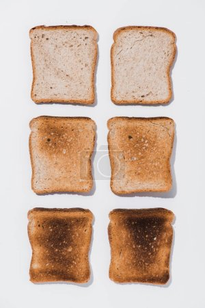 top view of rows of toasts in various roast stages on white surface