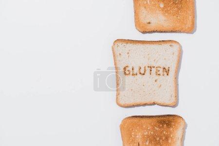 Draufsicht auf die Reihe von Toastbrot und Scheibe Brot mit verbranntem Glutenzeichen auf weißer Oberfläche