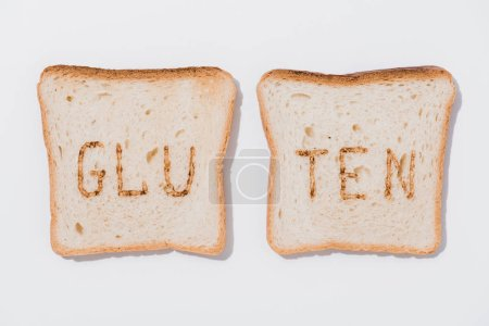 top view of slices of bread with burned gluten sign on white surface