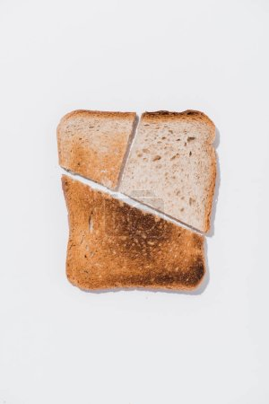 top view of slice of bread with roasted pieces on white surface