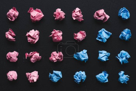 top view of arranged pink and blue crumpled paper balls on black background, think different concept