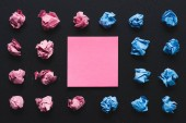 top view of pink and blue crumpled paper balls with sticky note on black background, think different concept