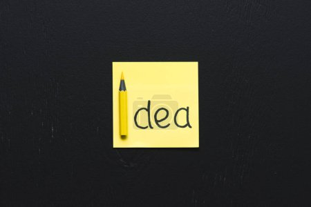 top view of 'idea' word written on yellow sticky note with black background, ideas concept