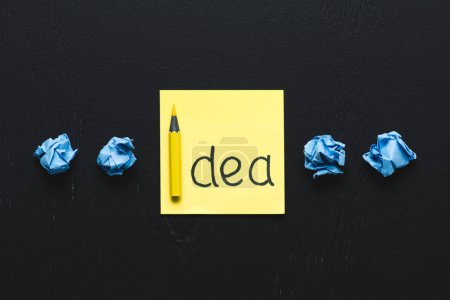 Photo for 'idea' word written on sticky note and blue crumpled paper balls on black background, ideas concept - Royalty Free Image