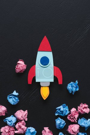 Photo for Cardboard rocket with pink and blue crumpled paper balls on black background, setting goals concept - Royalty Free Image
