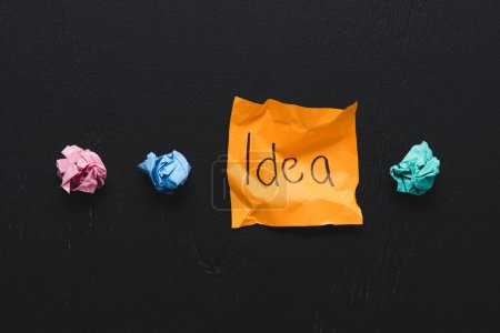 top view of 'idea' word written on sticky note with colorful crumpled paper balls on black background, ideas concept