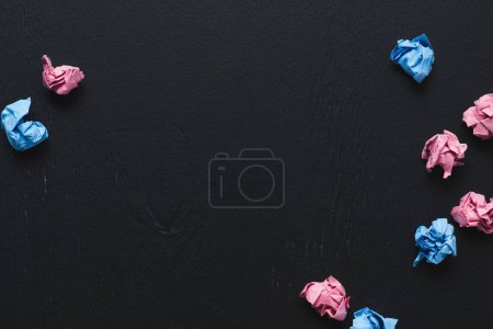 top view of scattered pink and blue crumpled paper balls on black background, think different concept