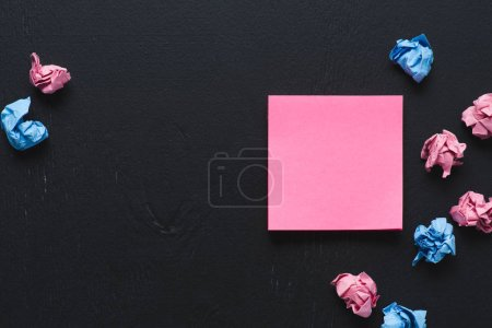 top view of scattered pink and blue crumpled paper balls with sticky note on black background, think different concept