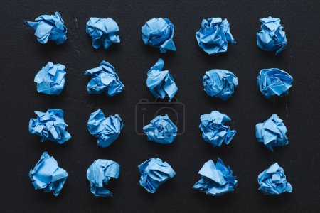 top view of blue crumpled paper balls on black background, think different concept
