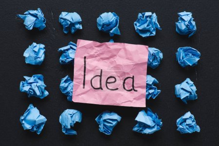 top view of 'idea' word written on sticky note with blue crumpled paper balls on black background, ideas concept